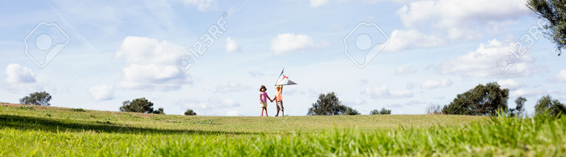 Brother and sister playing with a kite in the distance in a park on a sunny day